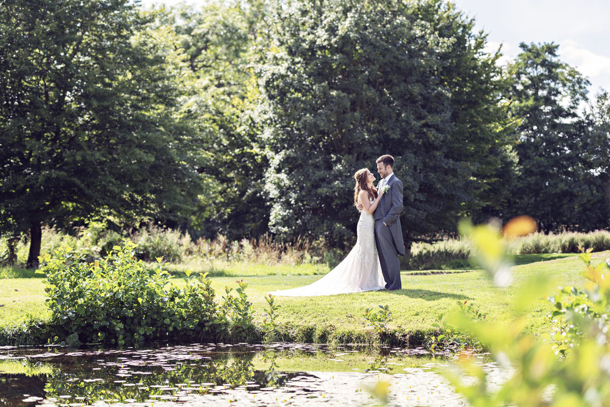 Across the pond, a bride and groom at Pryors Hayes Cheshire