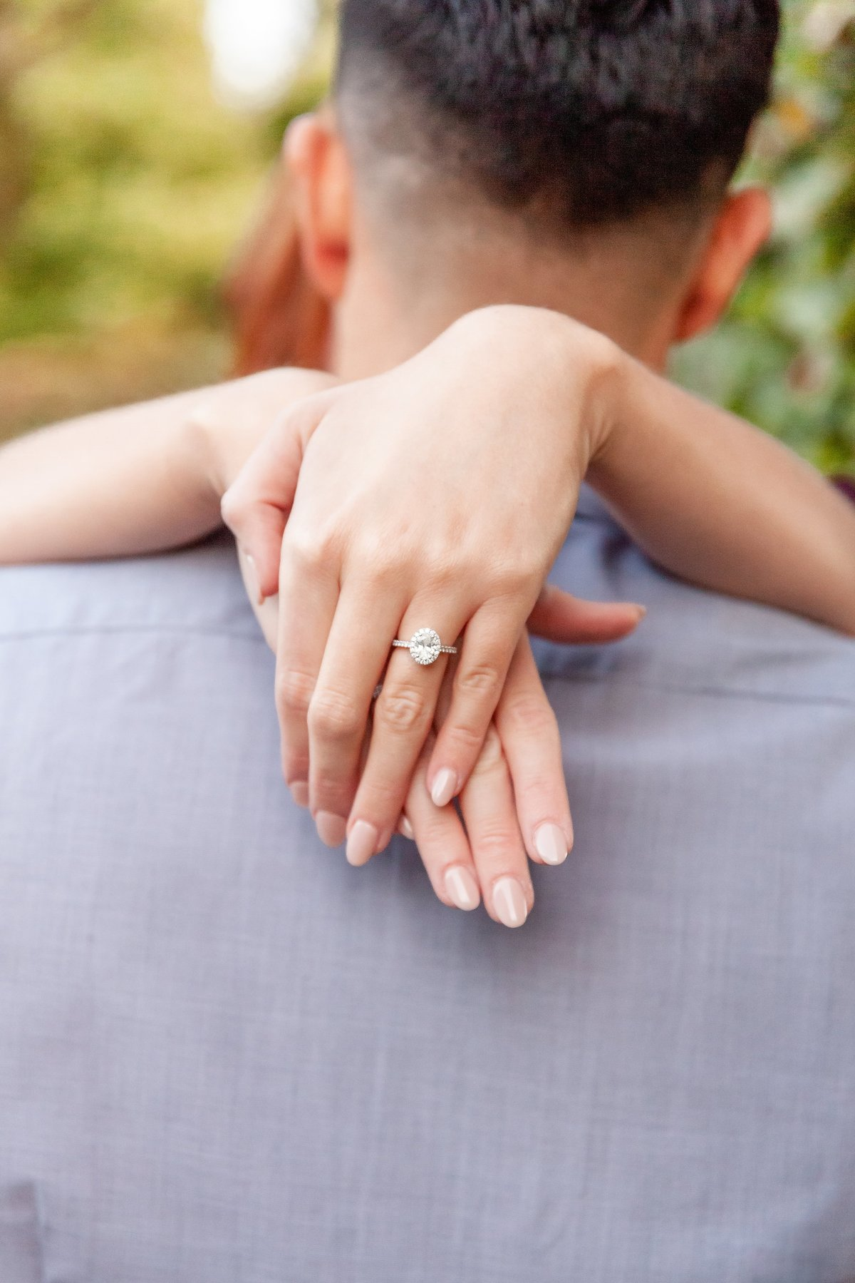 Girl-rests-arms-on-his-shoulders-and-shows-her-Engagement-ring-at-Niagara-Boutanical-Gardens