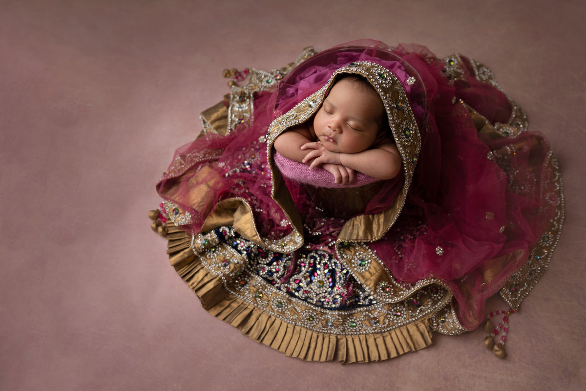 Baby girl wearing her mom's indian wedding dress
