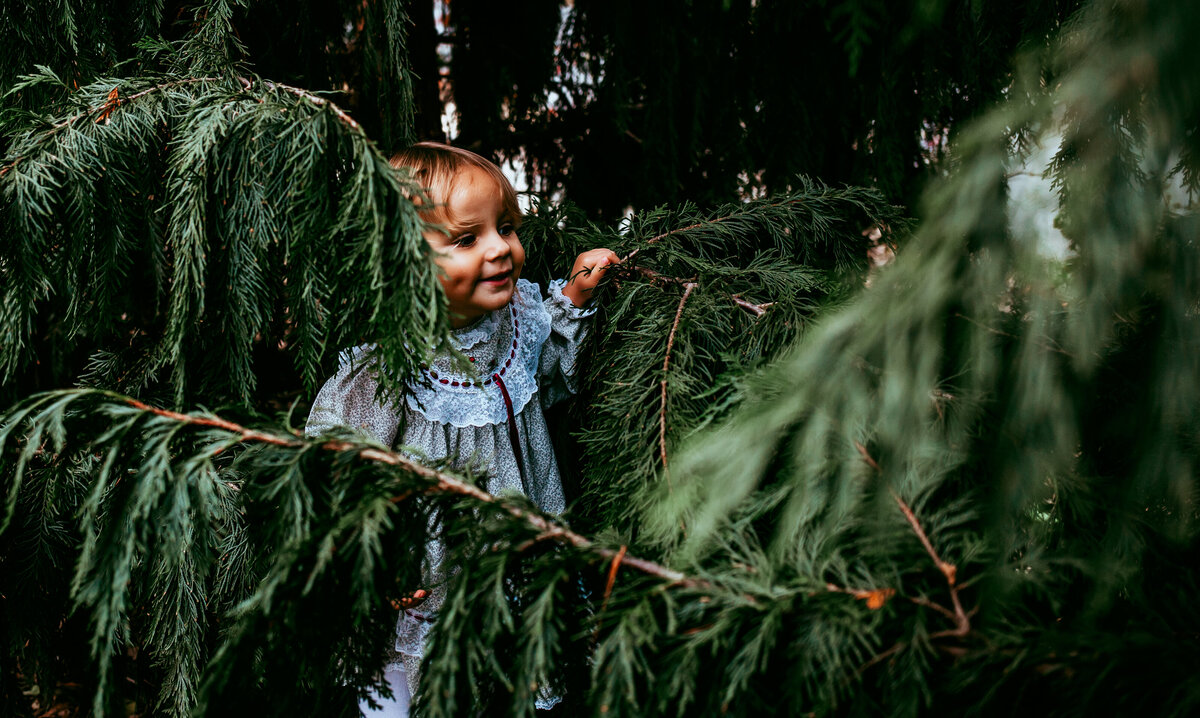 Little girl peeking out of the trees in Vienna Virginia