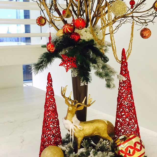 red and gold holiday decor inspiration with red tree cones, gold deer, large centerpiece with evergreen and red gold ornaments