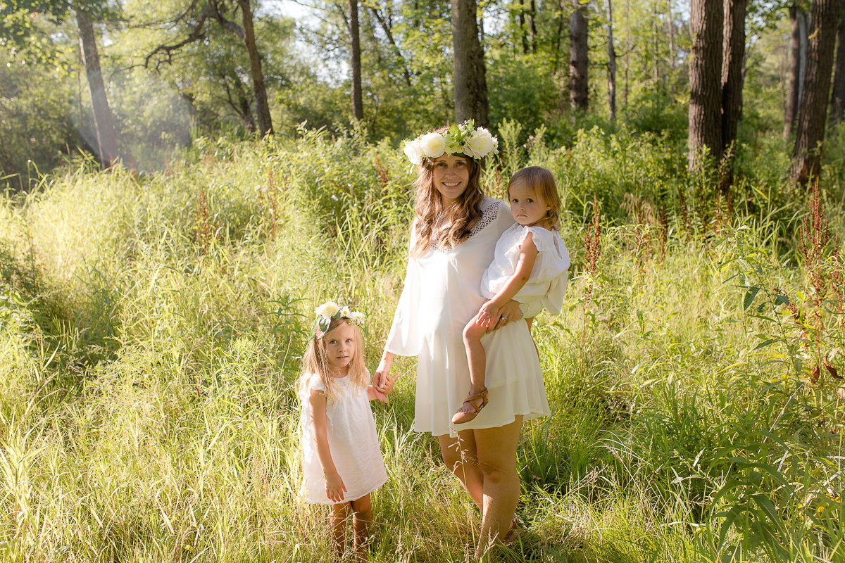pregnant mom standing with 2 daughter in sunny field {Oakville Family Photographer}