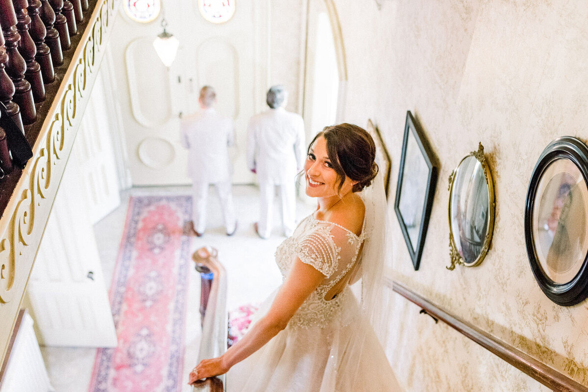 bride walks down the stairs for father first look