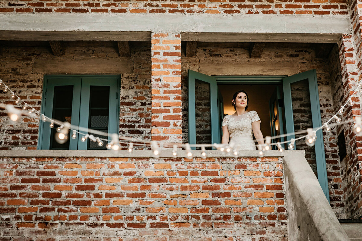 A picture of the bride in her wedding dress, standing in an open doorway on a vintage brick balcony as she pauses for a moment on her wedding day to look outside by Garry & Stacy Photography Co - Tampa wedding photographer