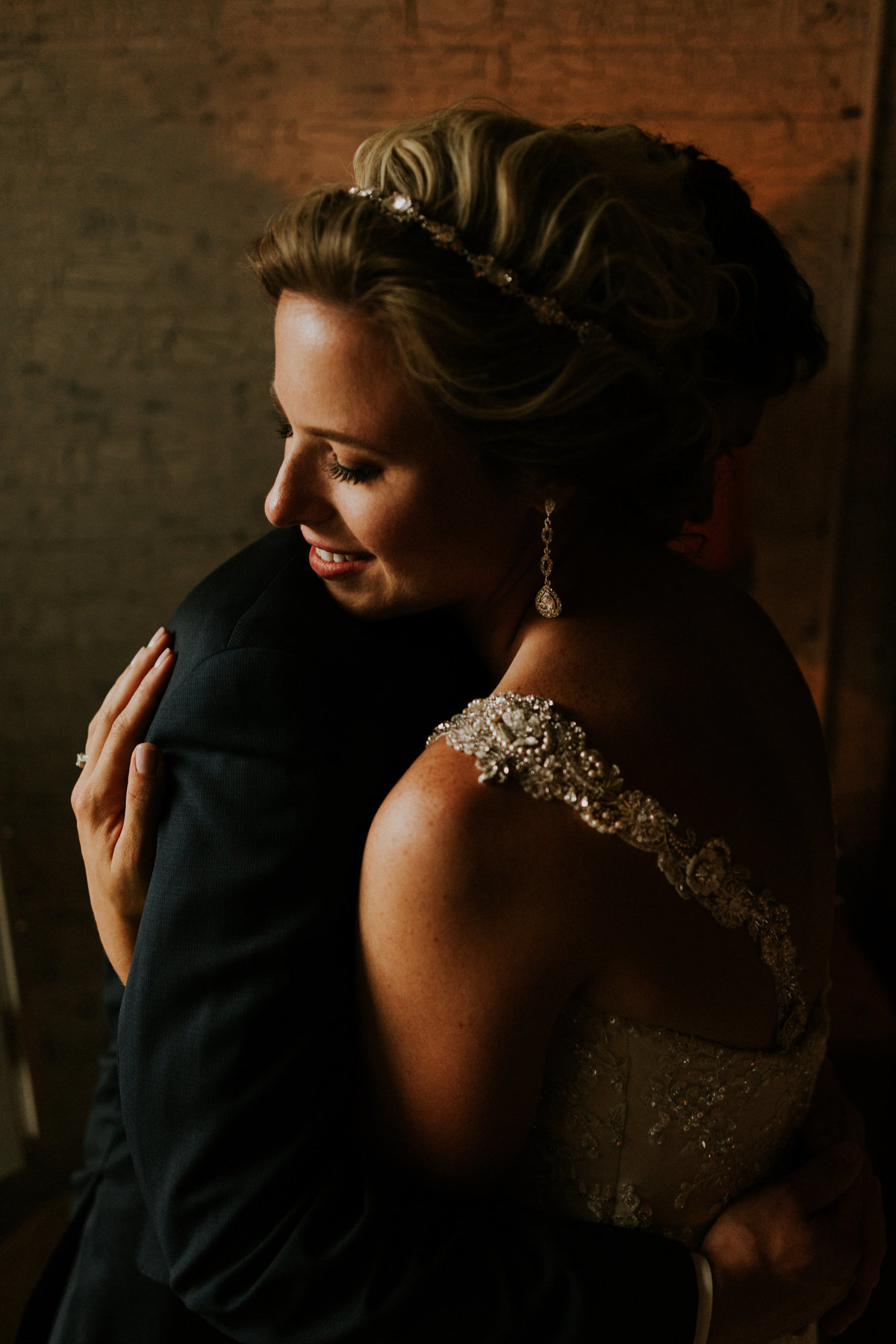 A bride and groom hug during their portraits for this unique photograph