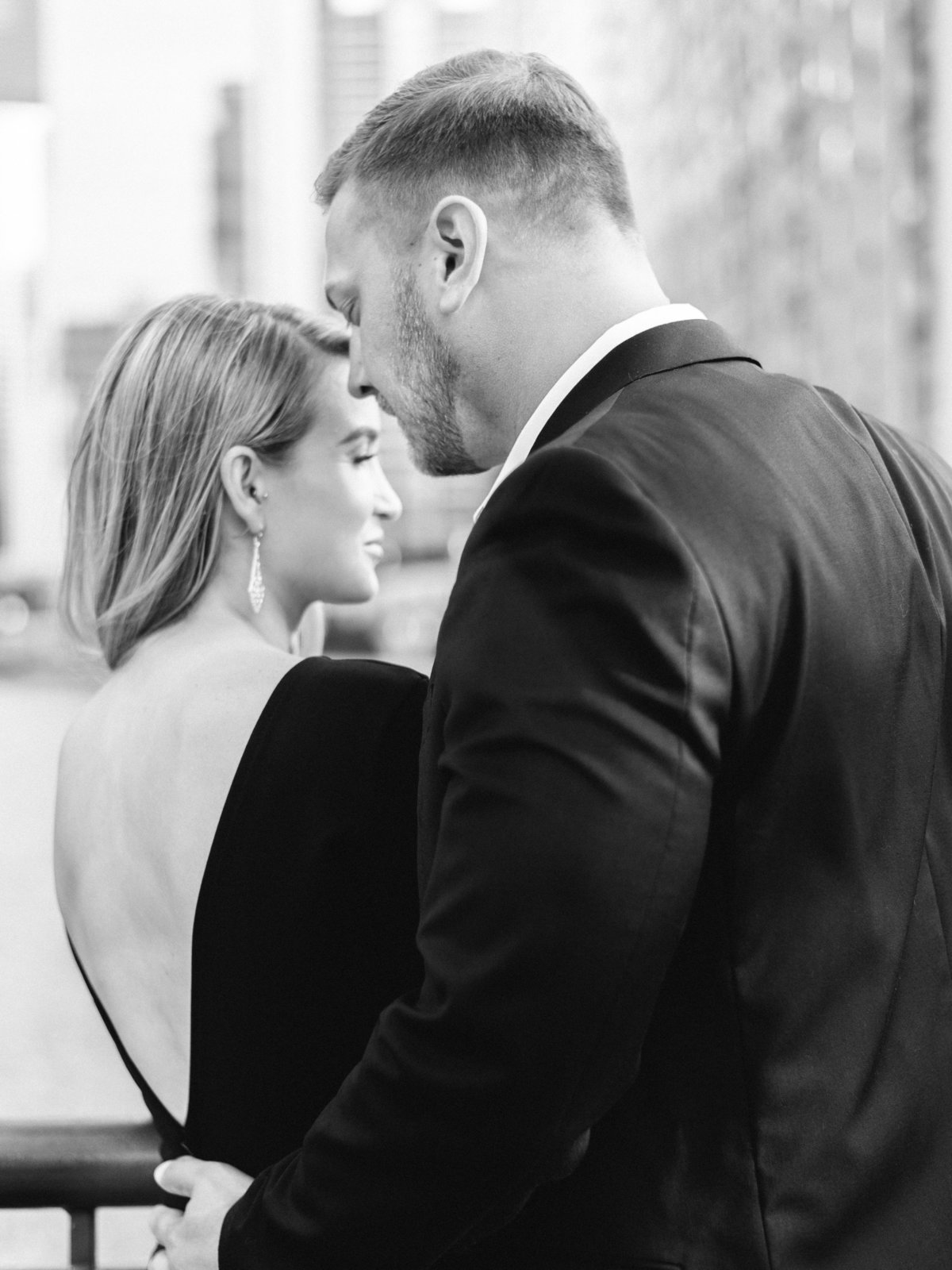 engaged couple wearing elegant suit and backless black dress