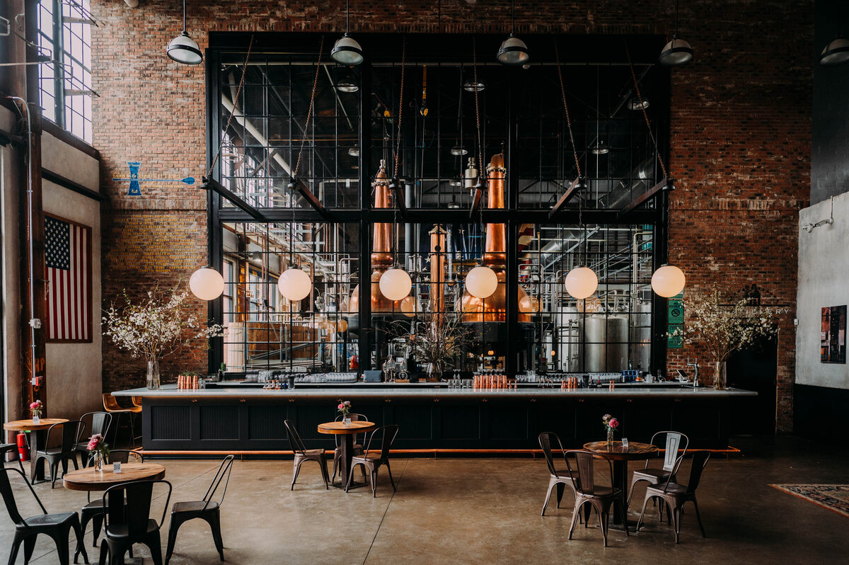 a photo of a naturally lit industrial space with small wooden tables and metal chairs in front of a marble bar with spherical cafe lights hanging from the ceiling in front of a brick wall with a window in the middle looking into a distillery. The venue is Philadelphia Distilling Company shot by philadlephia wedding photographer alex medvick