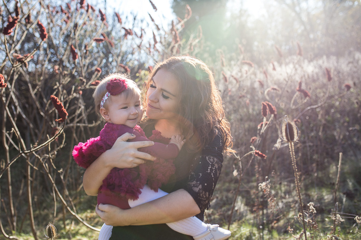 mother holding baby daughter in golden sunlight outdoors {Burlington Family Photographer}