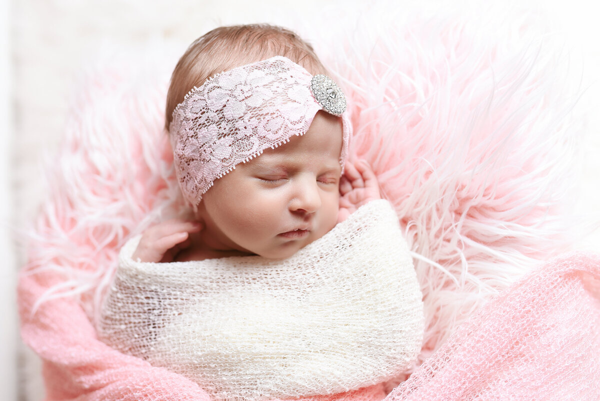 Beautiful Mississippi newborn photography: newborn girl wrapped in ivory with rhinestone headband in a pink flokati bed