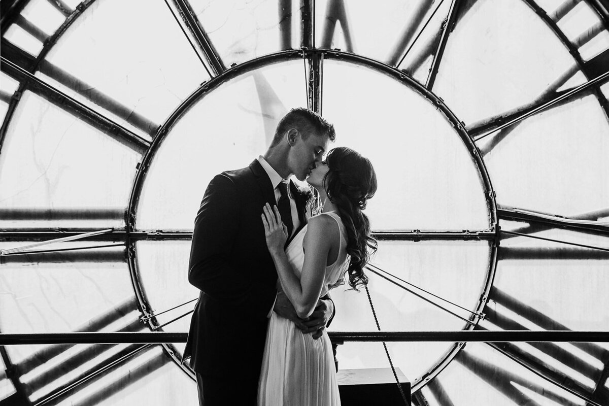 bride and groom kiss inside clocktower in denver black and white