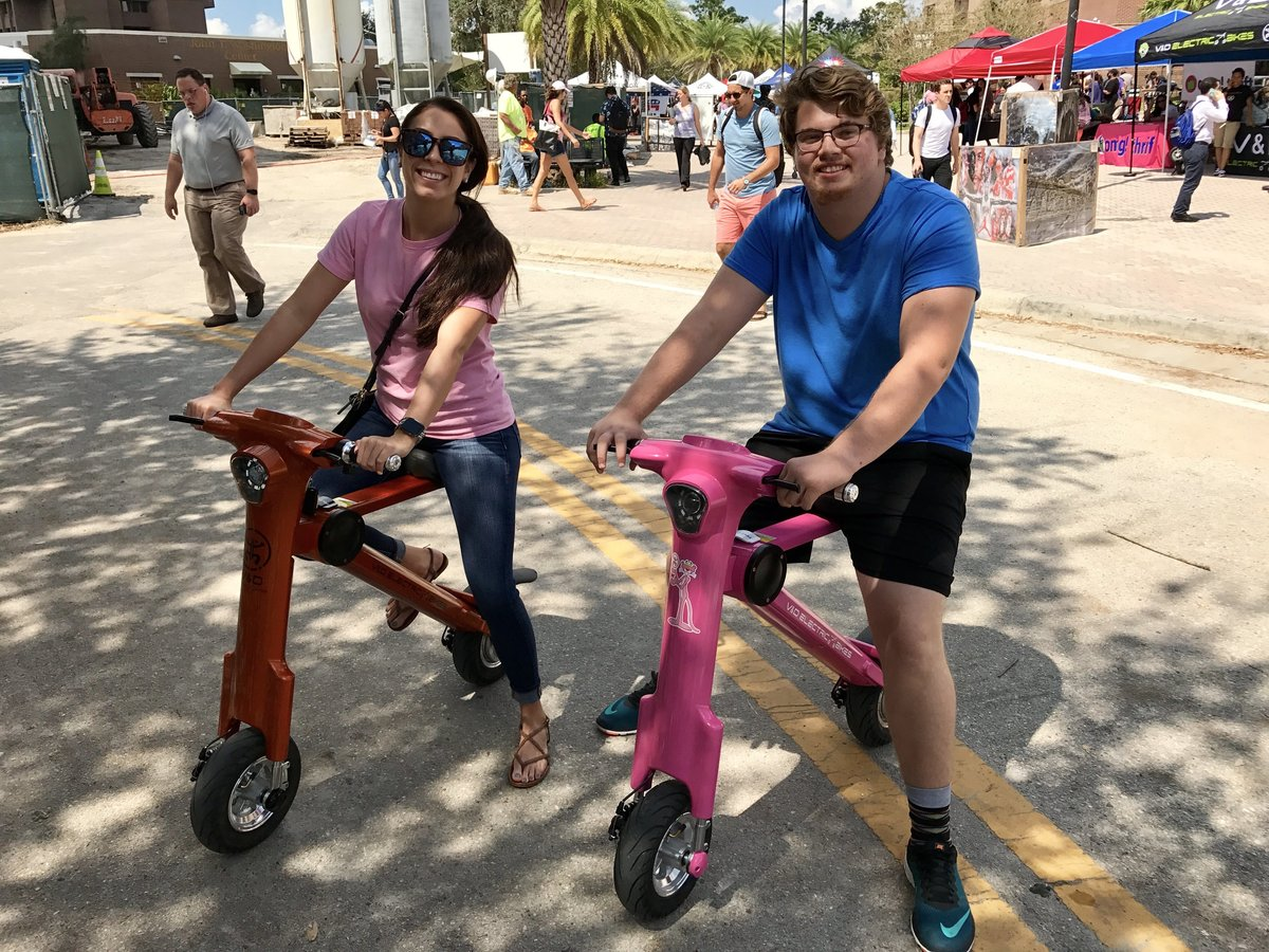 College couple sitting on Pink & Bronze Go-Bike M1