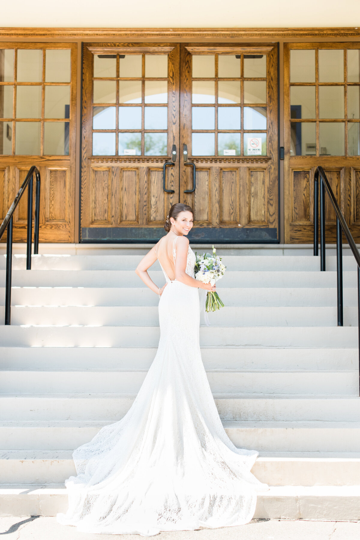 Bride standing on the steps of the old PACI, Thunder Bay Law School, while the train of her lace Mikaella gown trails down the steps