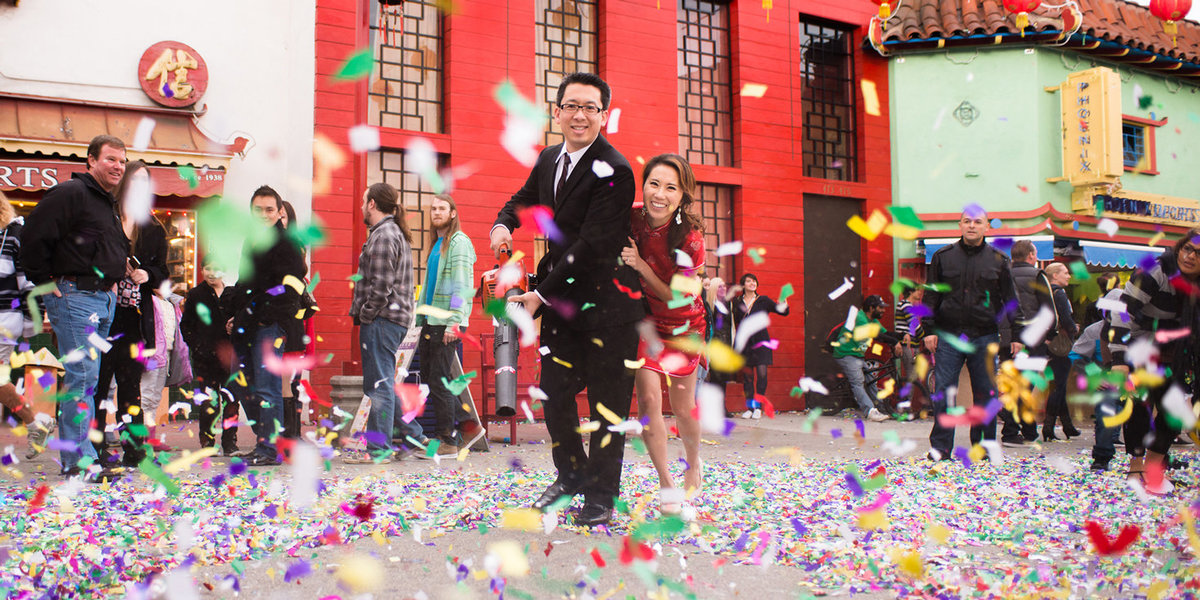 newlyweds shooting confetti towards camera on LA streets from ground angle