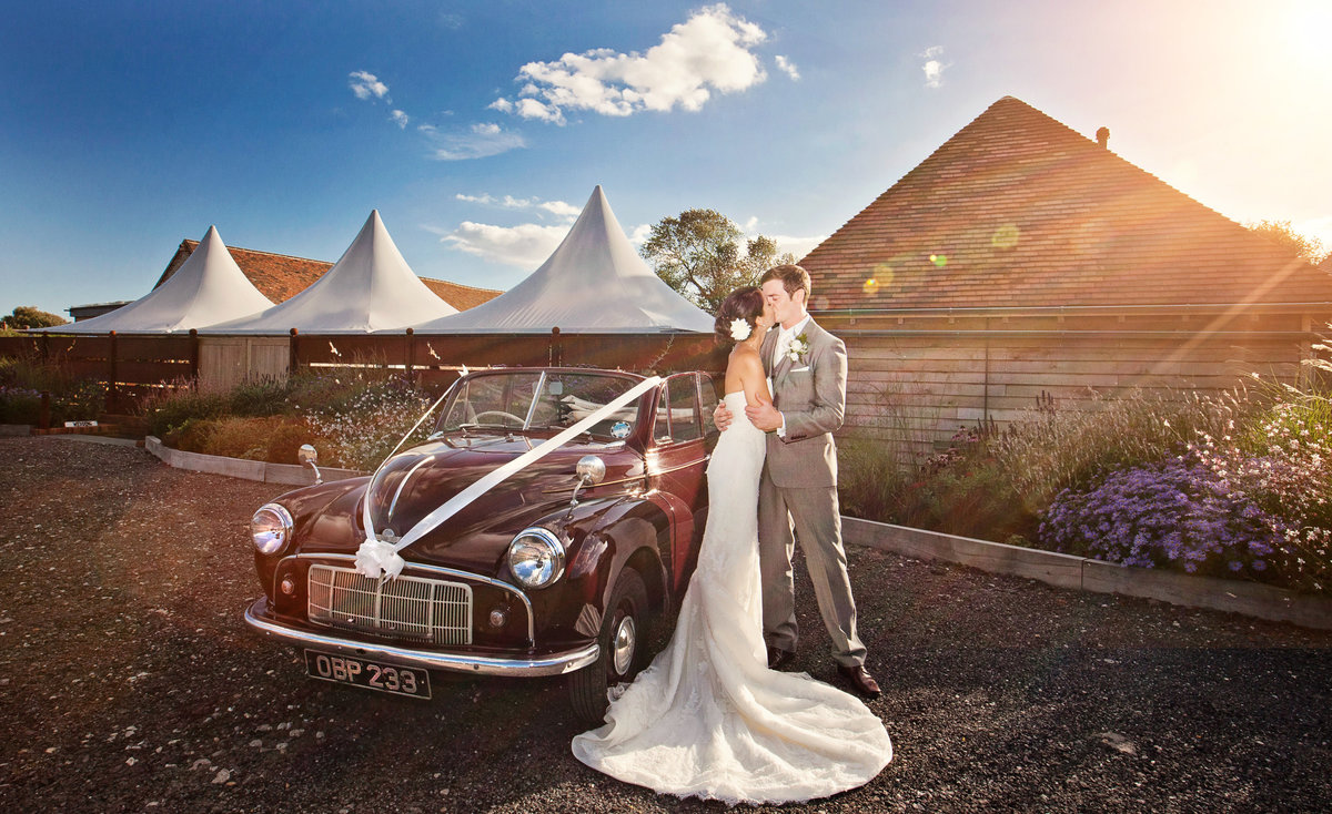 Wedding day photograph of the bride and groom next to their wedding car which is a burgundy morris minor in front of the southend barns wedding venue entrance with sun flare. Bride wears Pronovias gown