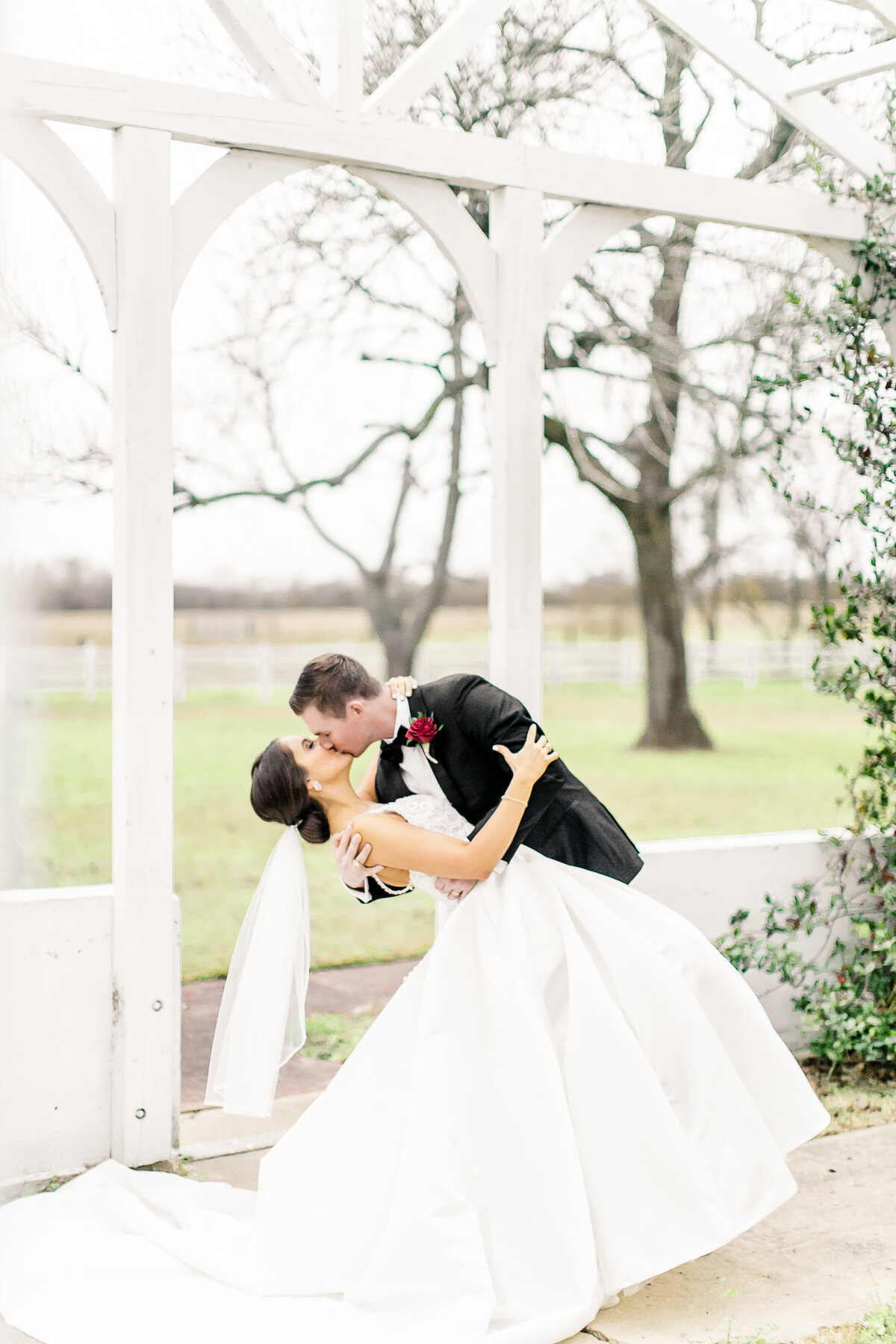 A bride and groom kissing on their wedding day underneath the Greenhouse Arbor at the Grand Texana's Wedding venue
