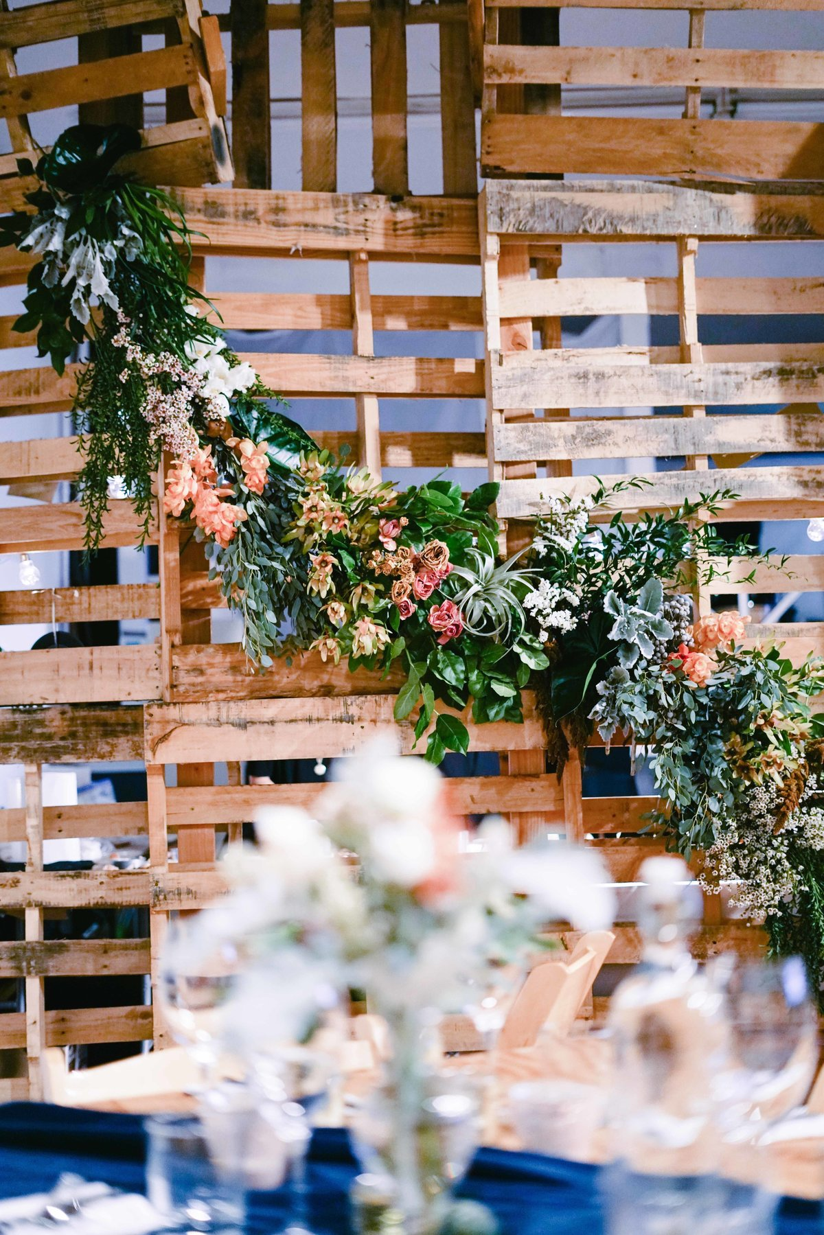 Dinner party backdrop using wooden pallets and long greenery garland with flowers