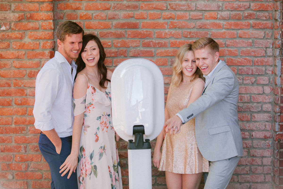 Two couples pose in front of a photobooth with a brick backdrop.