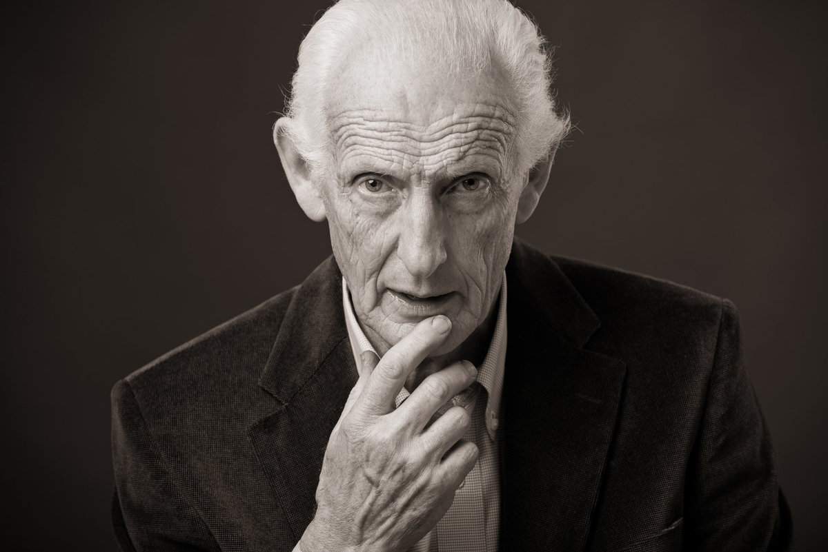 Black & white portrait of an elderly man looking serious with hand to mouth