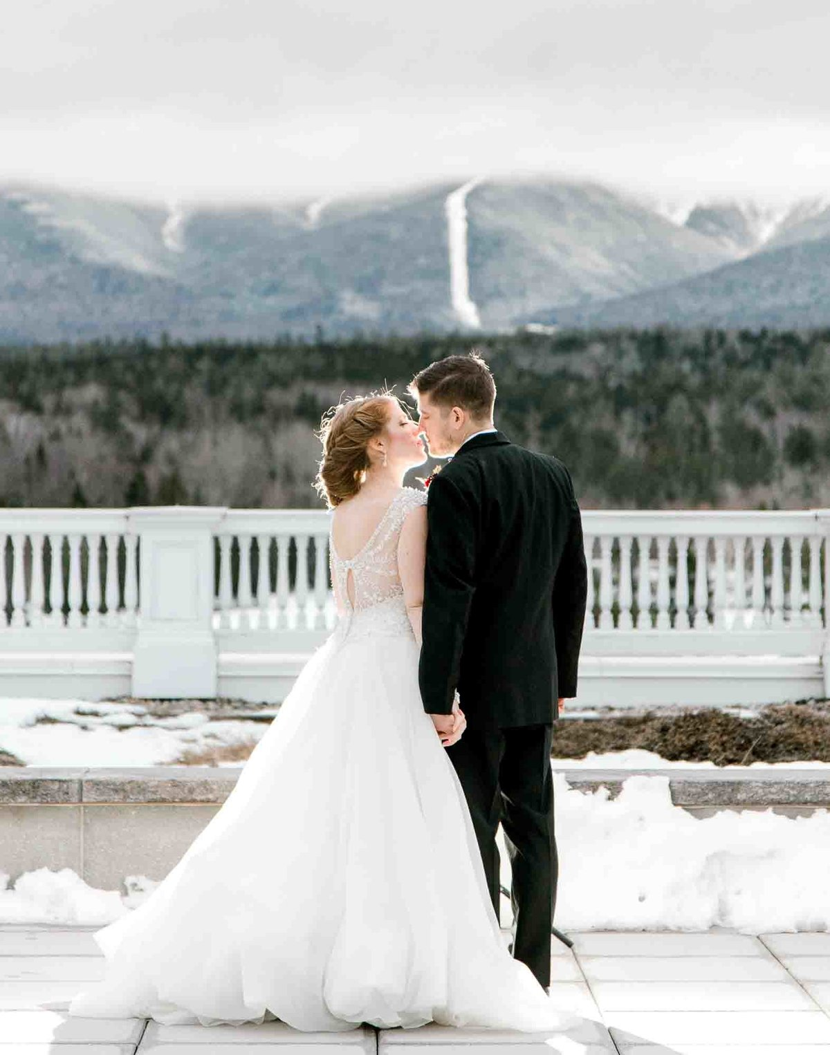 Bride and Groom kiss during their winter wedding at the Omni Mount Washington Resort.  Image by K. Lenox Photography