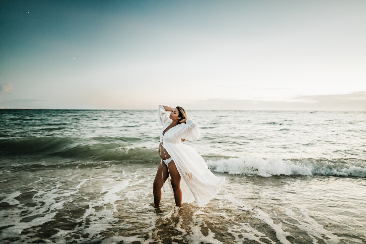 Okinawa Maternity Photographer, Mom to be on the beach letting the wind blow her dress with her baby belly showing