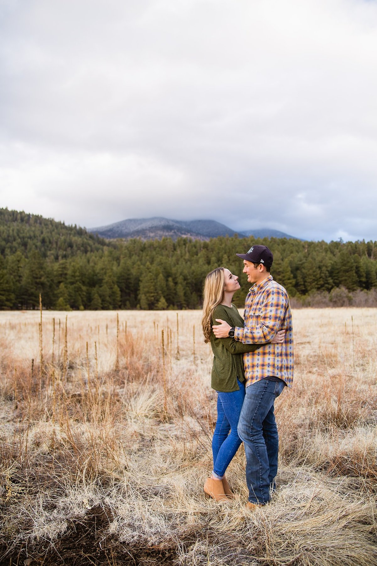 Multi-cultural couple looking at each other in a field during their adventure engagement session in Flagstaff, AZ by PMA Photography.