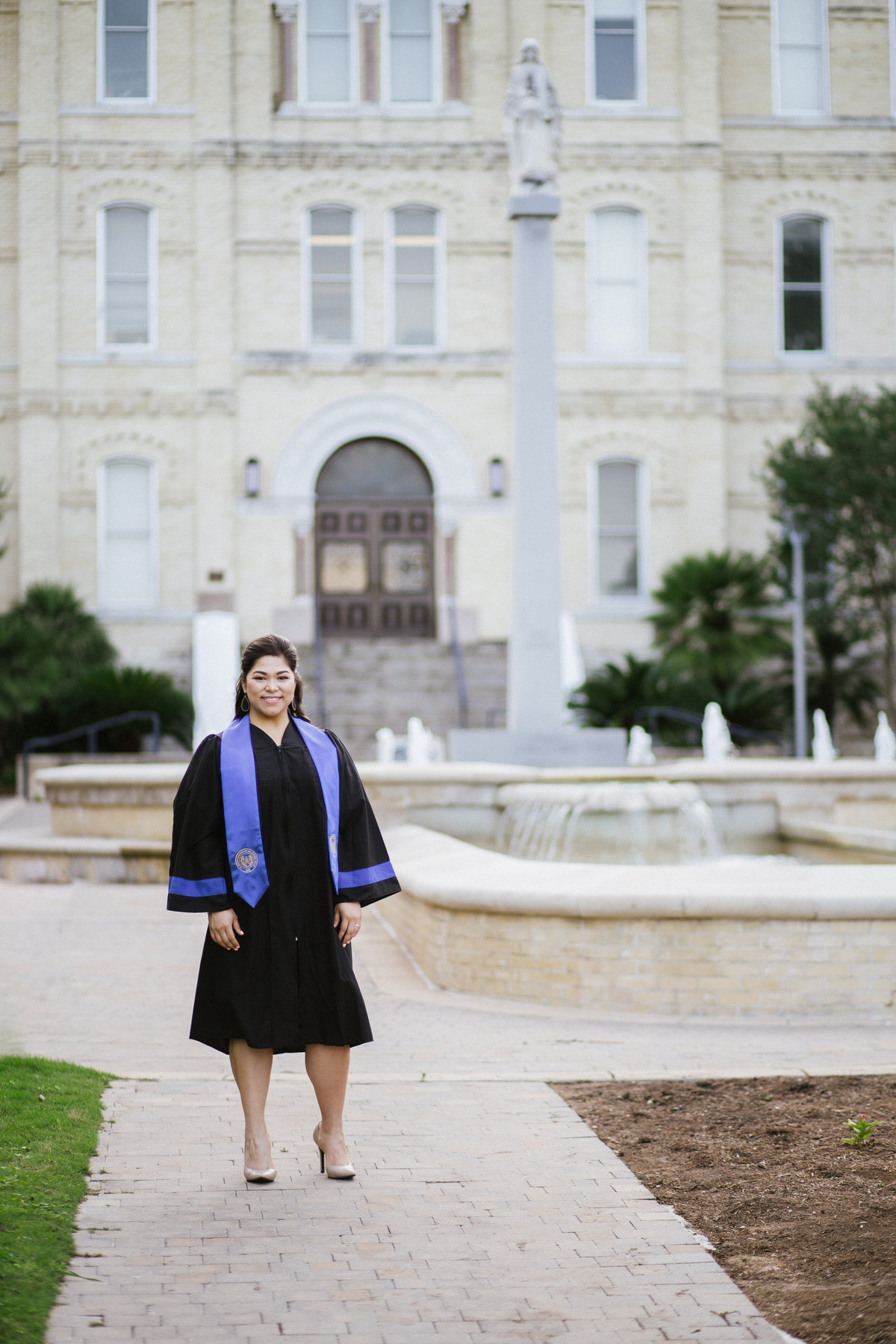 college senior standing by her university by San Antonio photographer