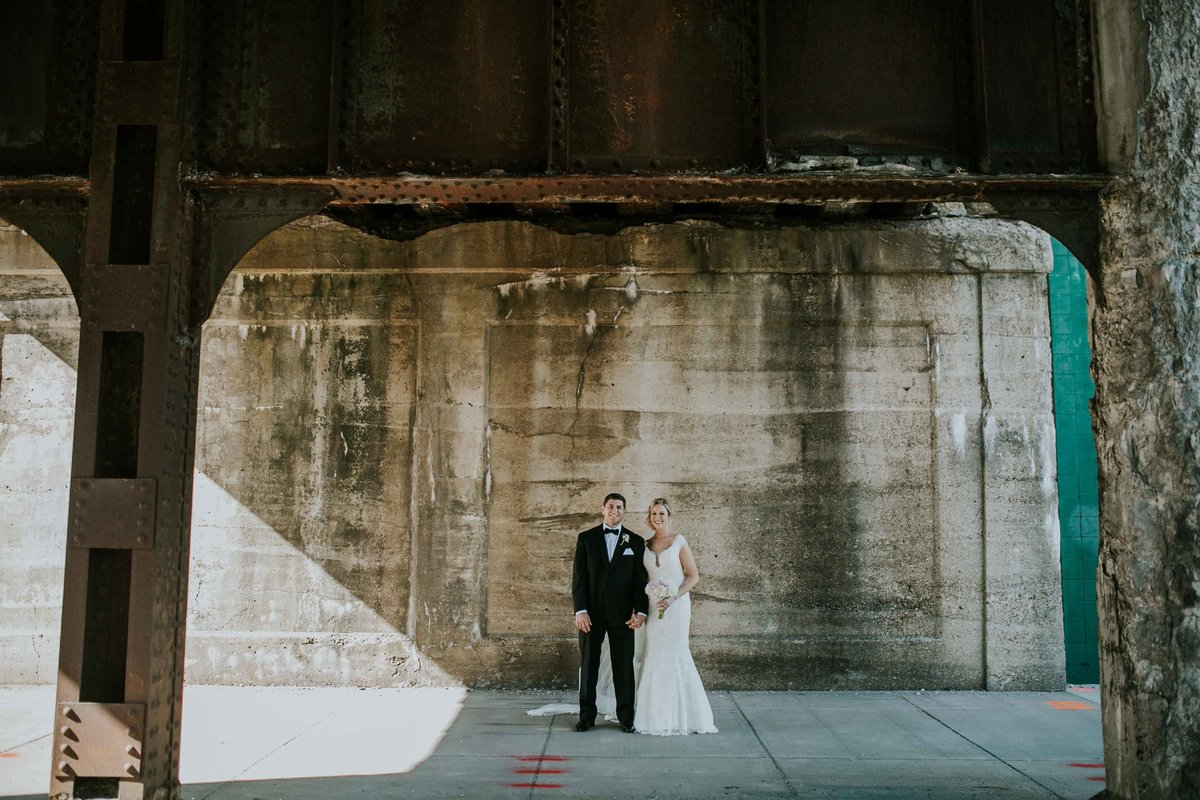 Couple stands under a bridge near Alexander Hotel Wedding