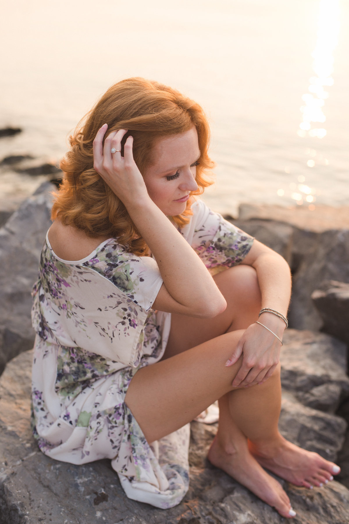 redheaded girl sitting on rocks by the water at sunset