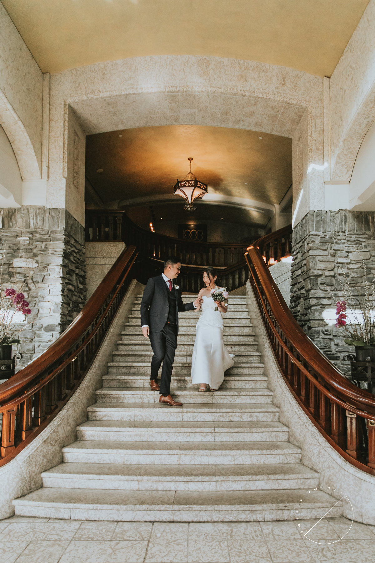 Bride and Groom coming down staircase inside the Banff Springs Hotel by Twenty Twenty Photography