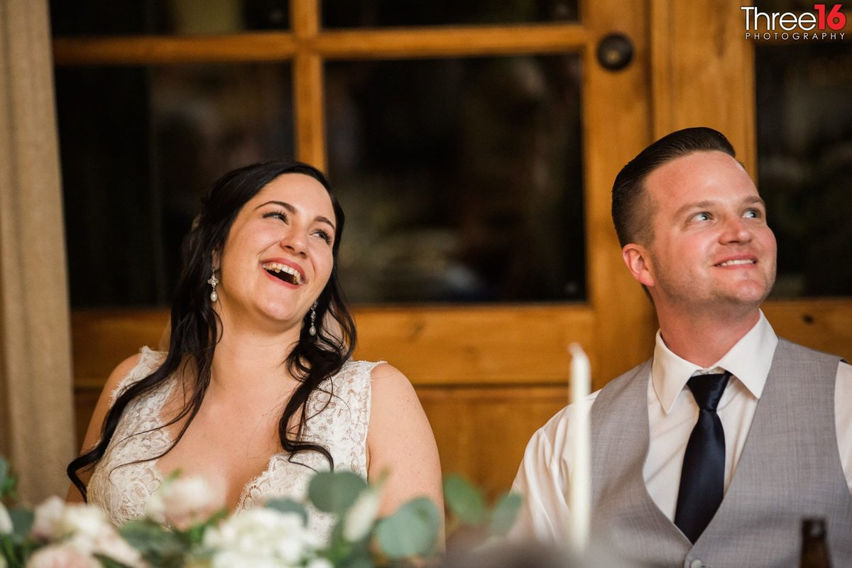 Bride and Groom laugh during the toast