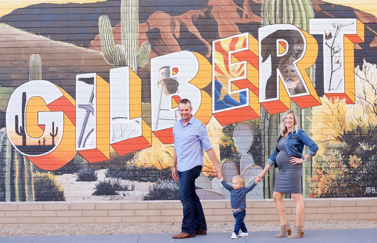 family in front of gilbert sign