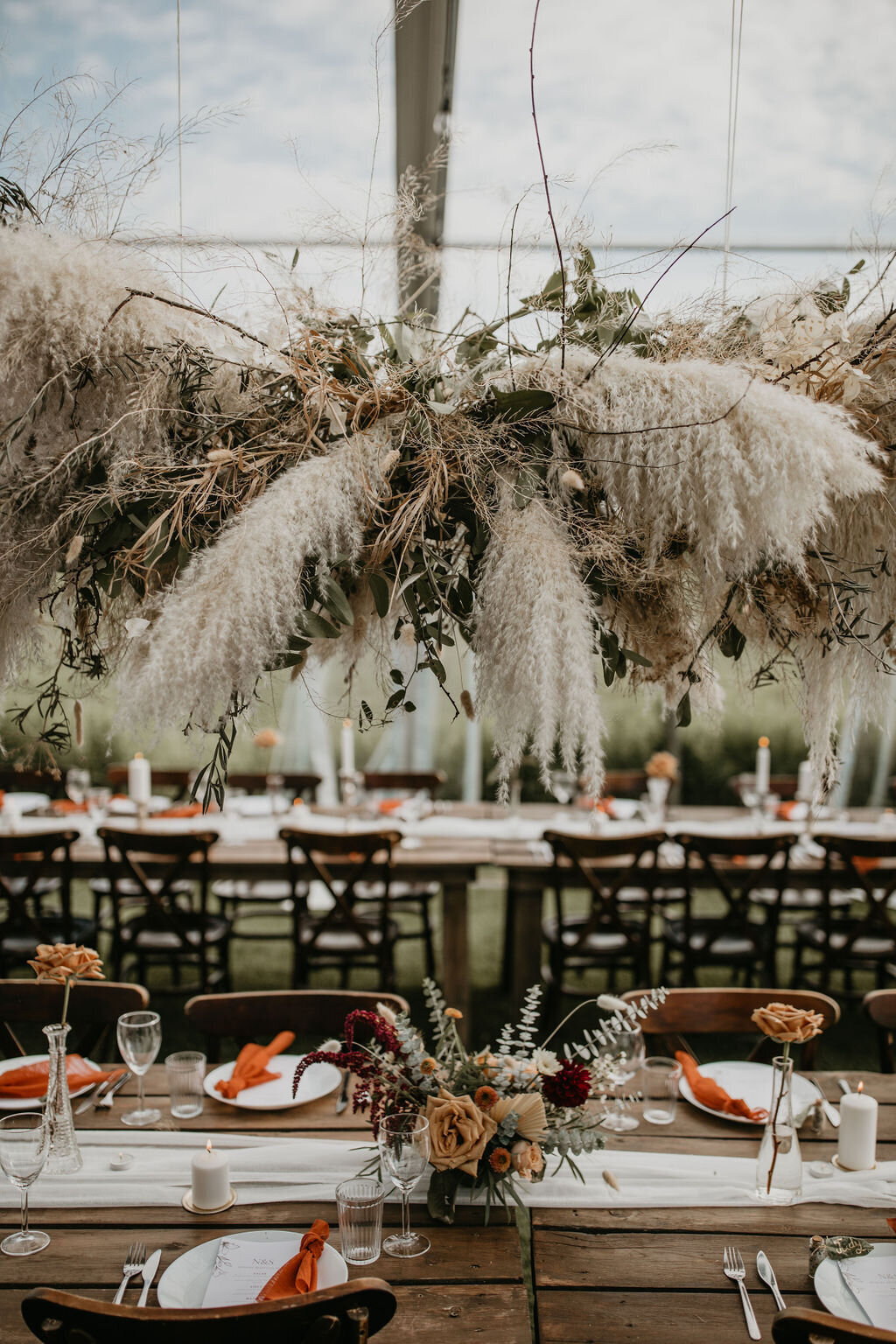 hanging floral piece in an clear tent with wood tables and chairs