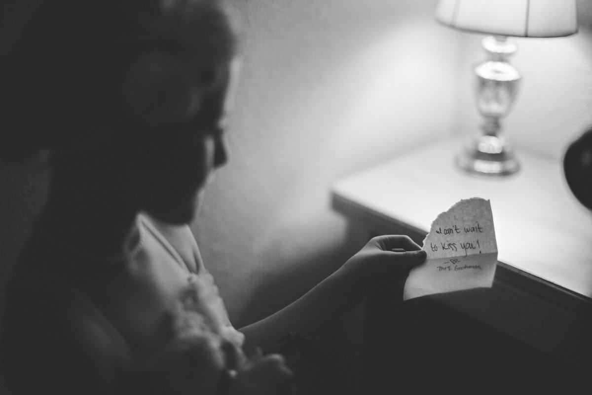 Bride at Vista West Ranch writes a quick note to give to groom while getting ready for wedding ceremony.