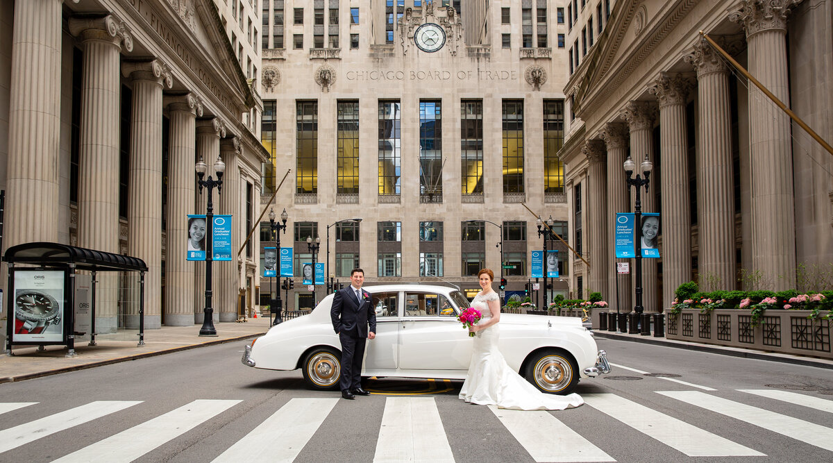 A bride and groom with a vintage car parked in the middle of the street at the Chicago Board of Trade building.