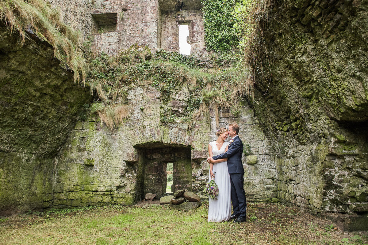 bride wearing a beaded column style wedding dress with sleeves, holding a wild flower bouquet, standing with her husband in a navy suit in the ruins of Minard Castle, West Kerry