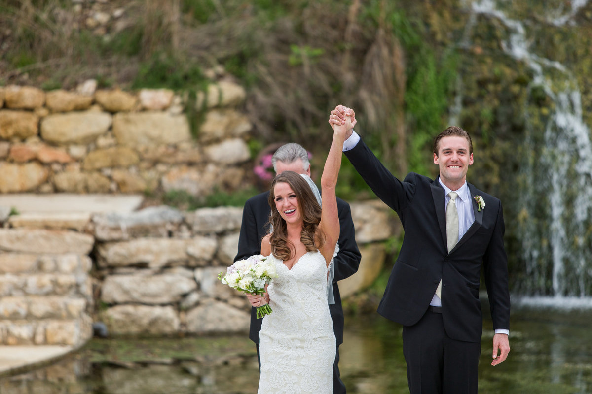 groom raising brides hand after ceremony with smiles on their face at Remi's Ridge at Hidden Falls wedding venue