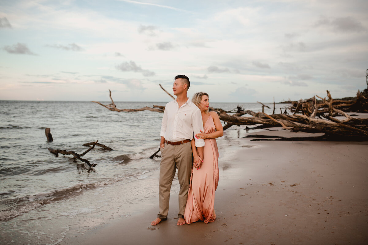 Professional wedding photographer takes photos along boneyard beach in Jacksonville, FL.