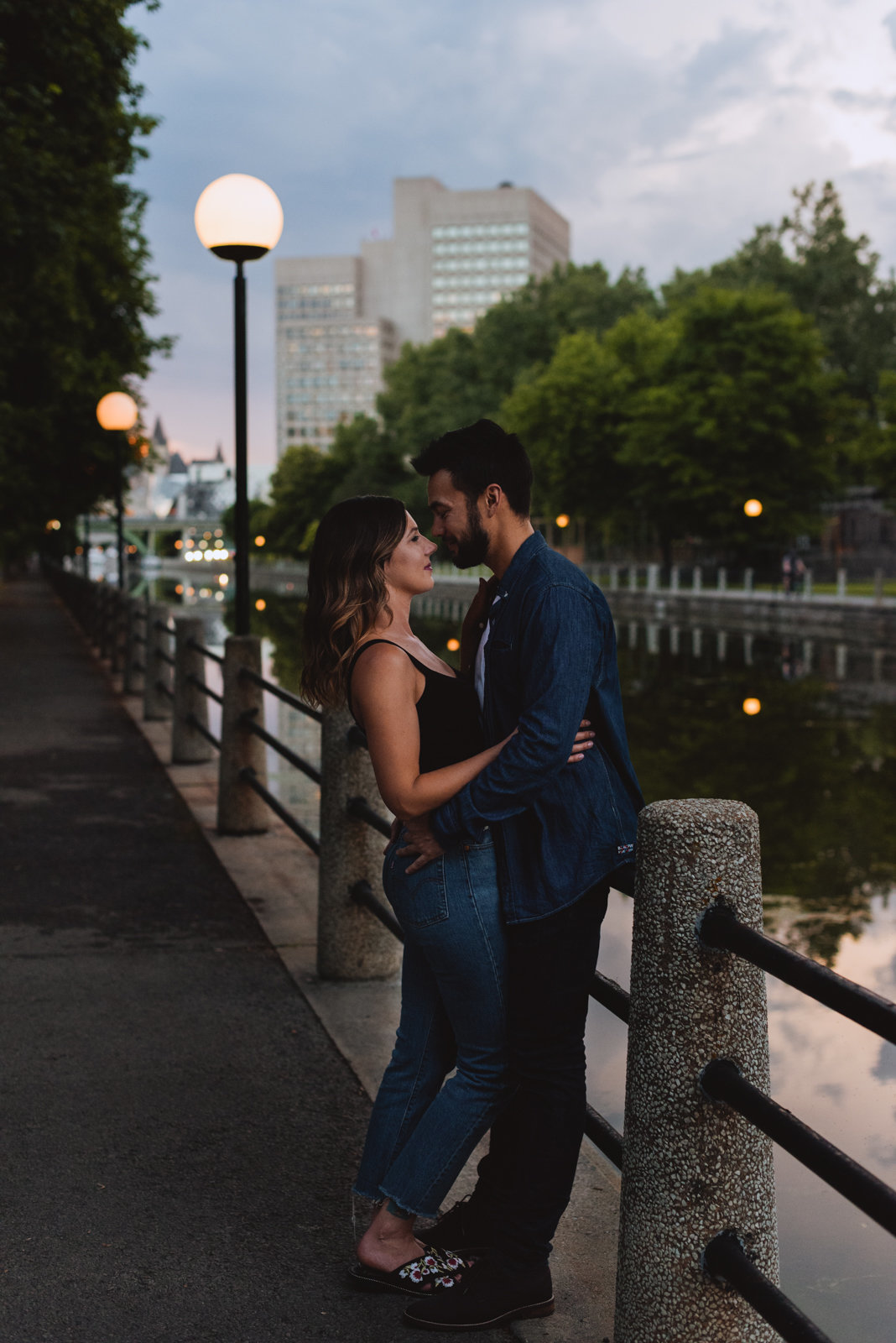 engaged couple by the canal at sunset