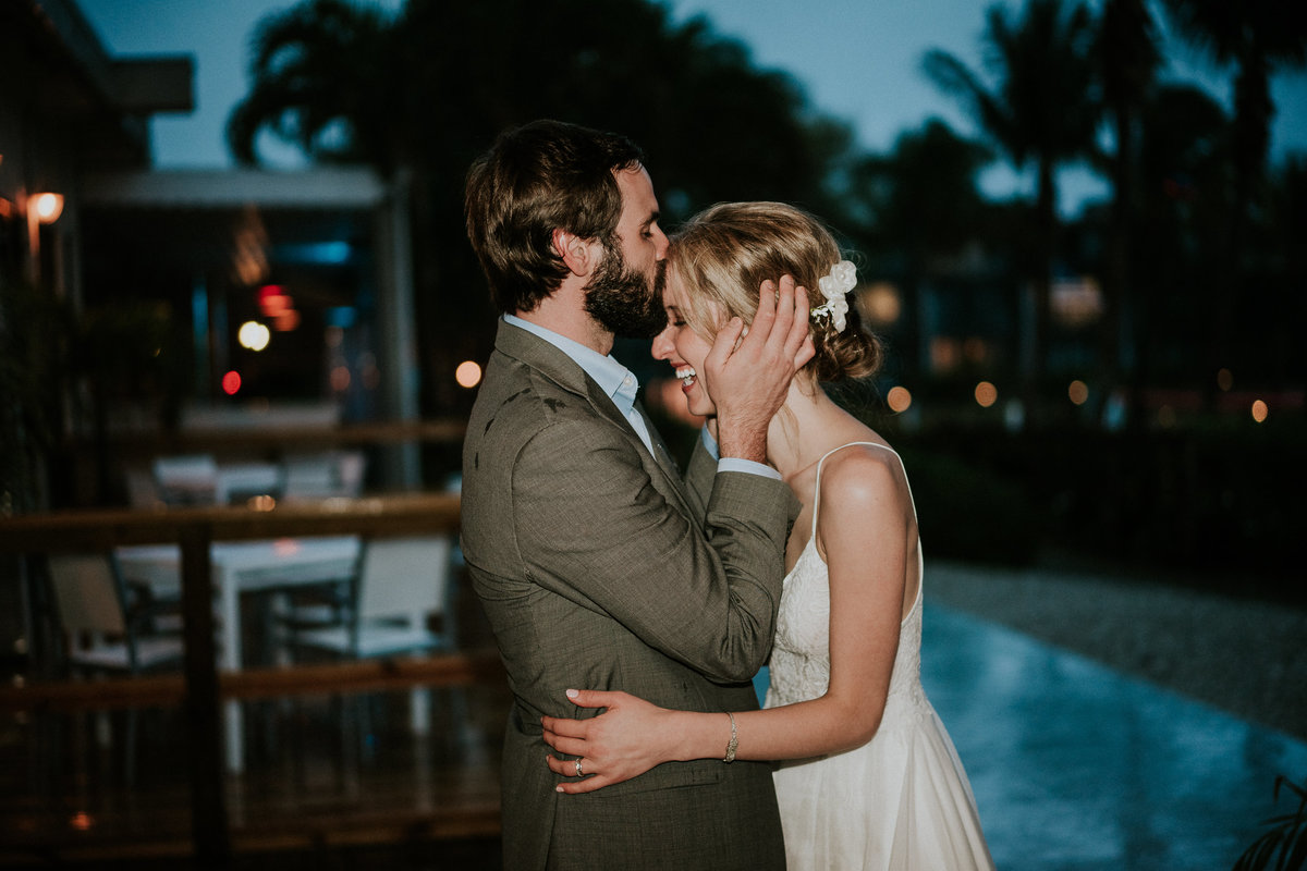 Groom holds bride's face and kisses her forehead in the rain on wedding night at Sandpiper Bay Club Med