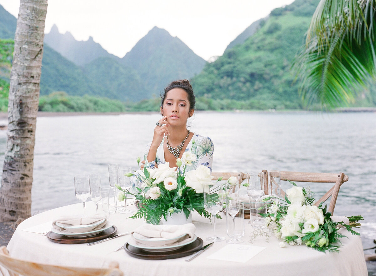 Vahine elegant portrait in Tahiti during a pre wedding shooting with table design and flowers and tahitian pearls