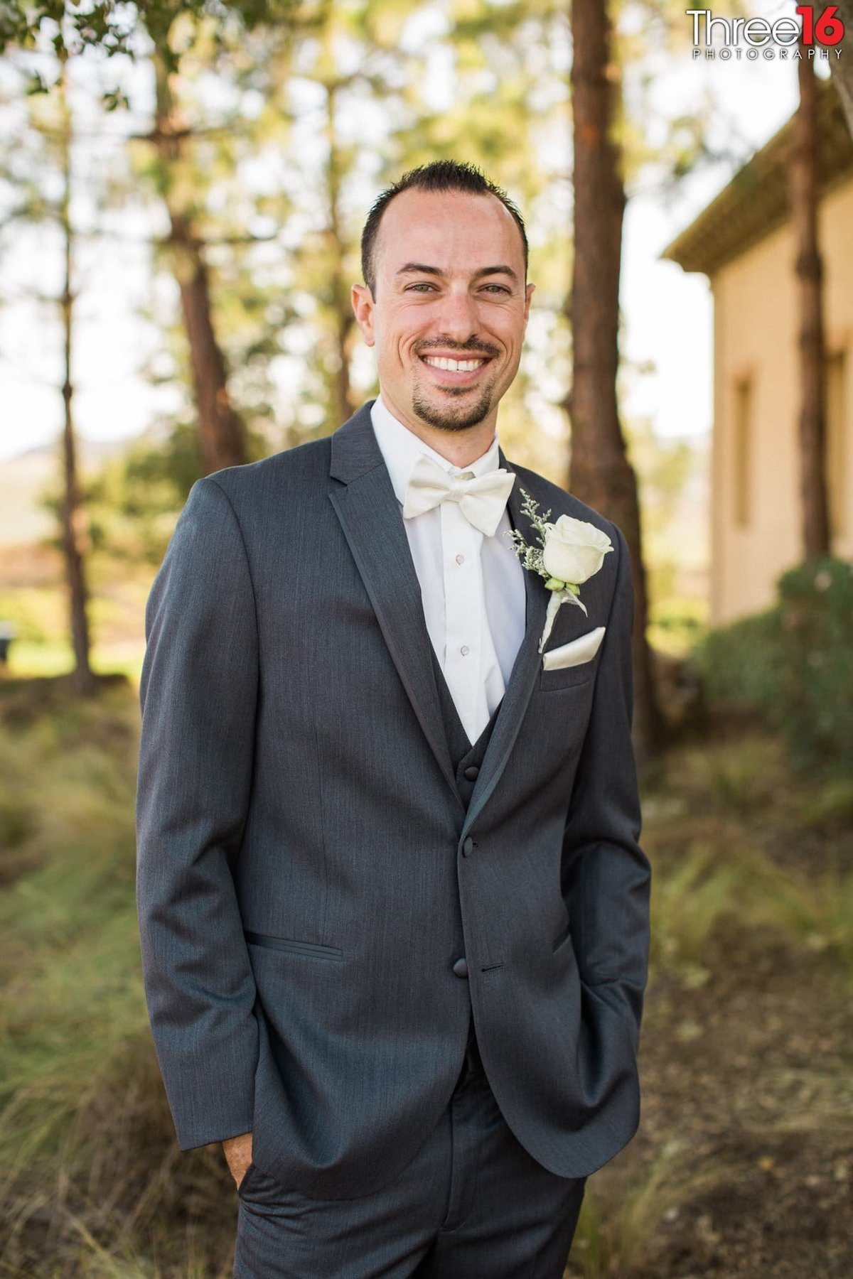Groom posing with his hands in his pockets and big smile