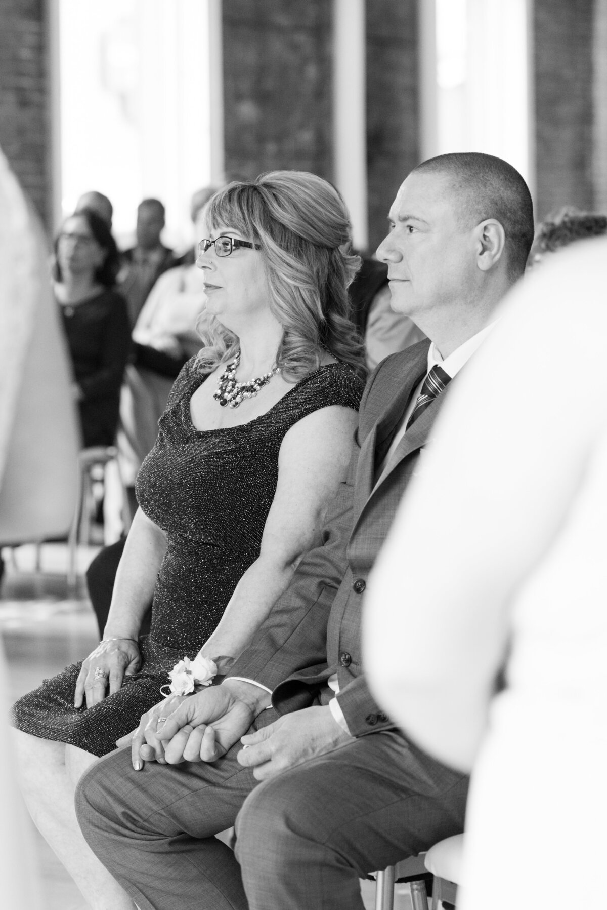 Mom and dad hold hands as they watch their daughter get married during her wedding at The Chanterelle in Thunder Bay