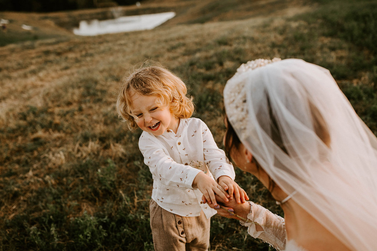 A bride holding a little boys hand.