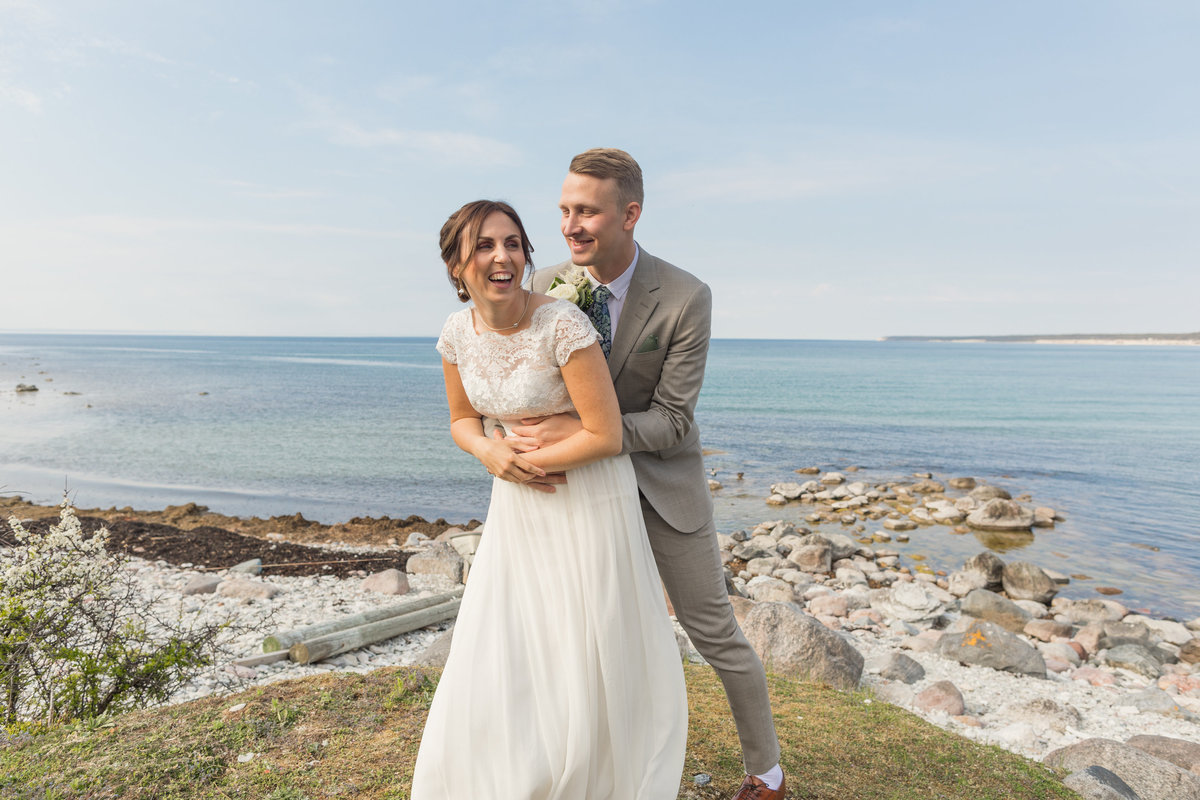 a weddingcouple in Gotland with the groom hugging his wife from behind tickeling her so that she is laughing heavily