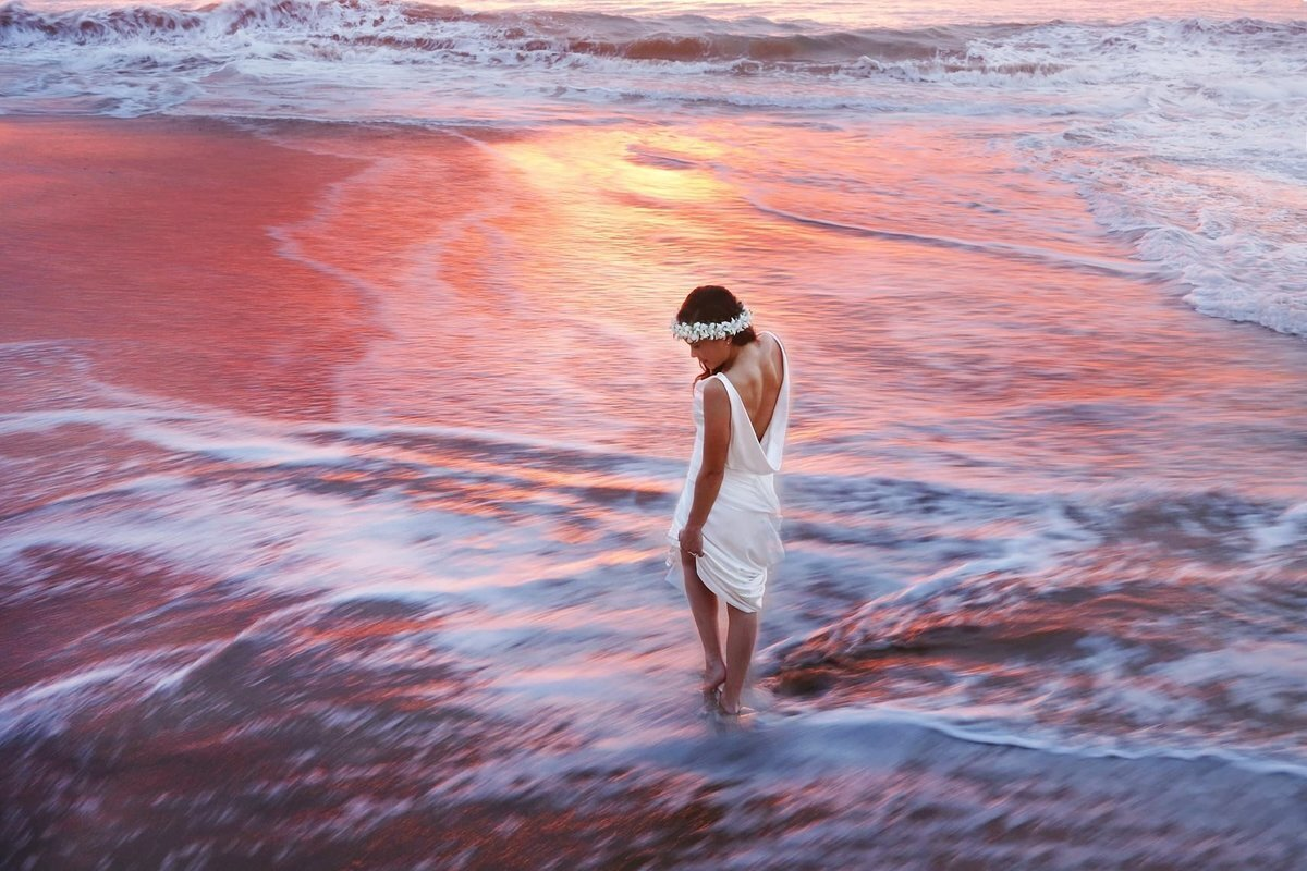 Dramatic bridal portrait of woman standing in the water at Maluaka Beach on Maui