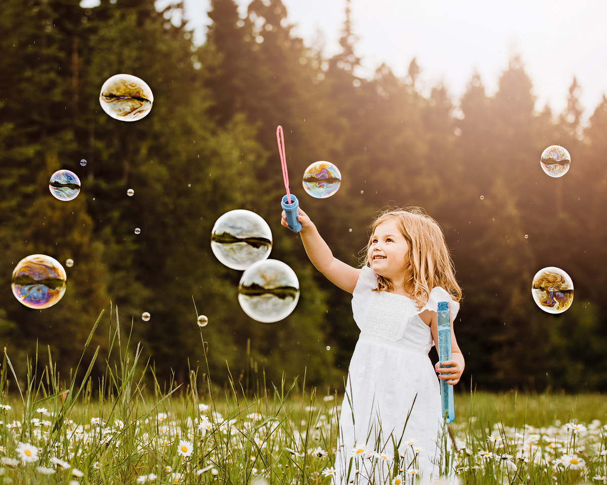 Young girl playing with bubbles in a field of flowers in Ellensubrg Washington