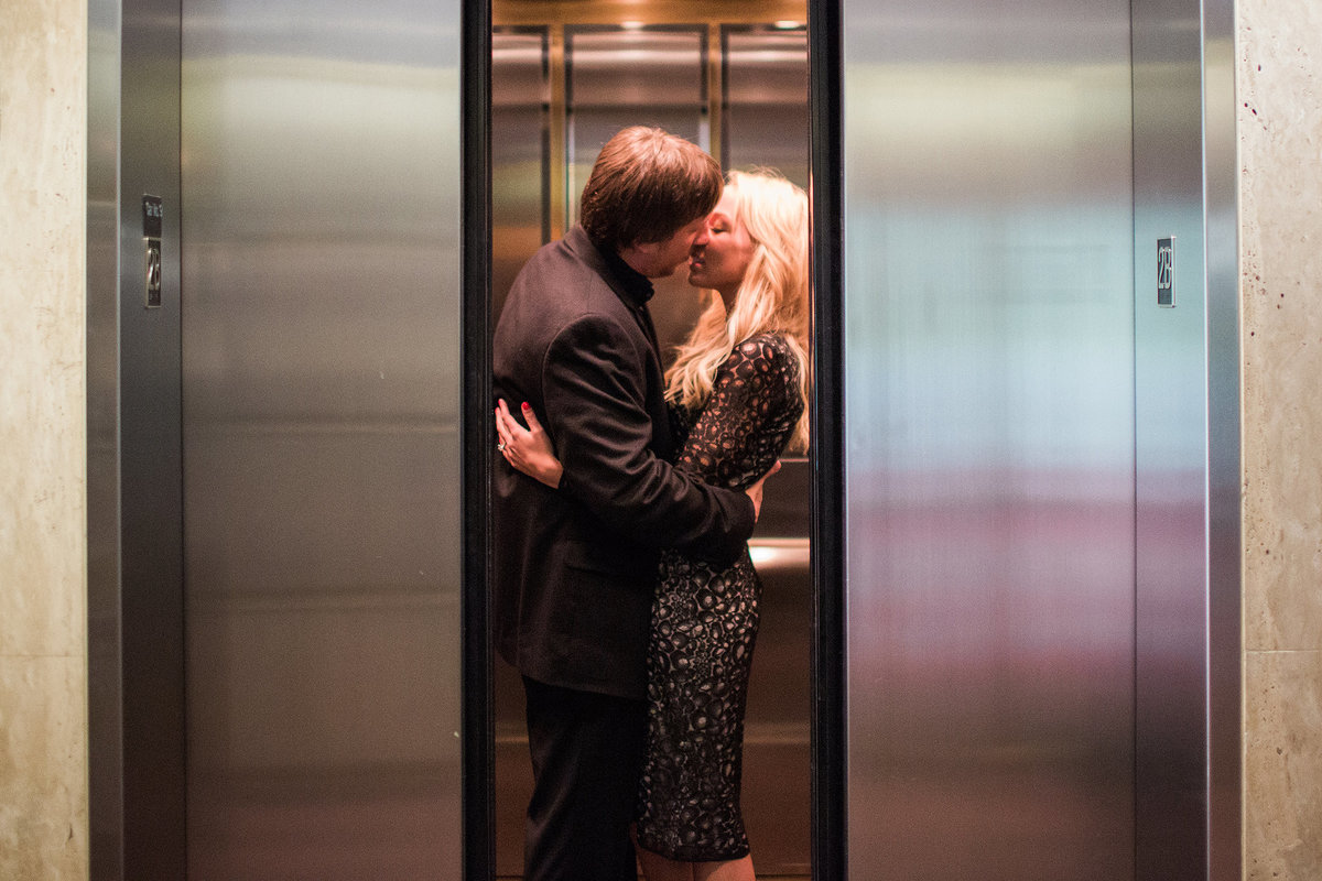 couple kissing through closing elevator doors during their engagement photographs