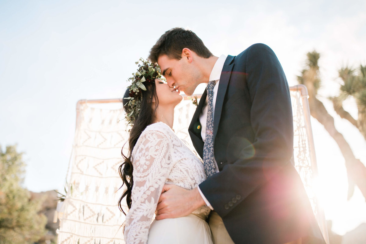 the bride and groom share their first kiss during their joshua tree elopement. the sun glows behind them.