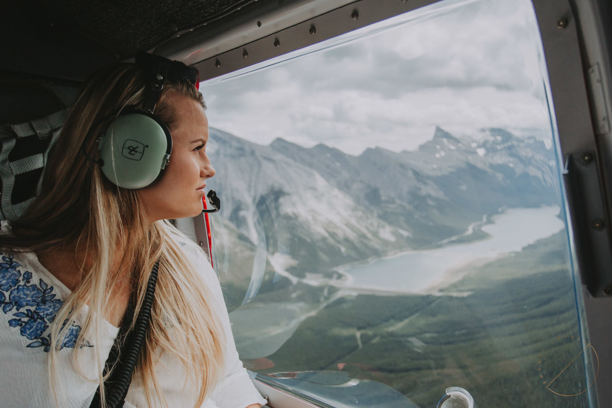 photo of client looking out helicopter window over the Canadian Rocky Mountains