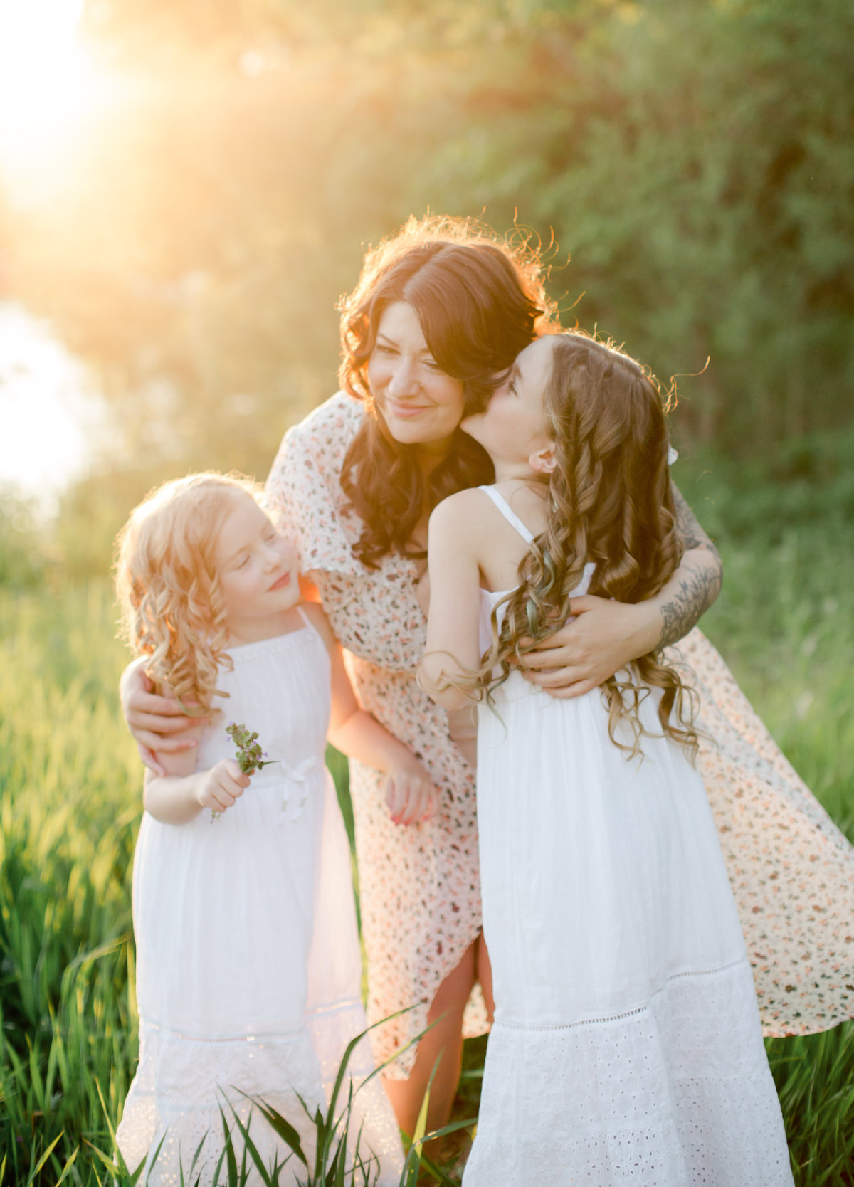pregnant mom hugs her daughters in grass fields of summer lake rochester minnesota